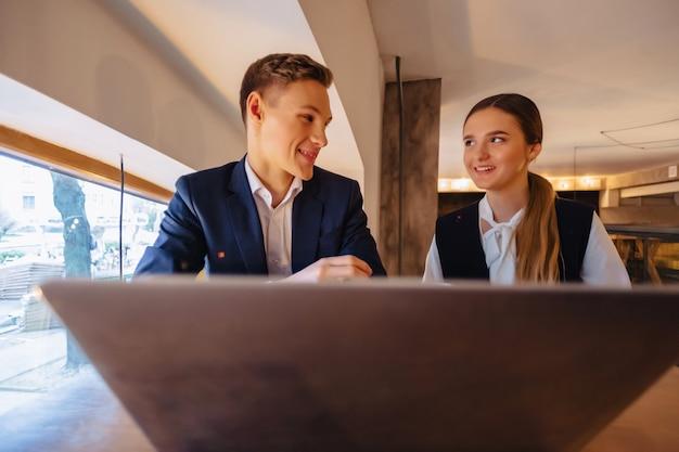 Um casal elegante bebe café da manhã no café e trabalha com um laptop, jovens empresários e freelancers