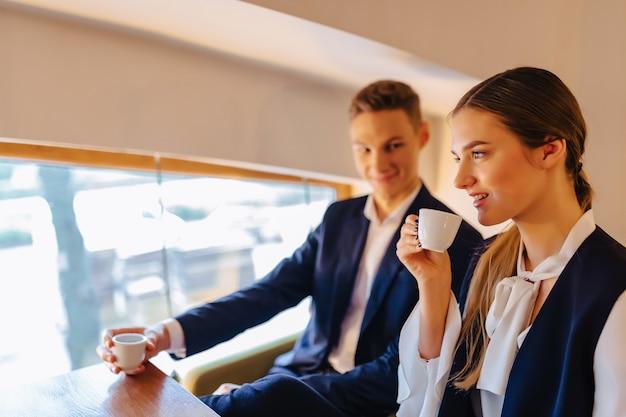 Um casal elegante bebe café da manhã no café, jovens empresários e freelancers