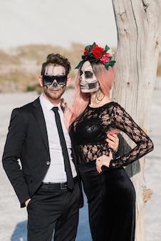 Um casal elegante com um esqueleto maquilagem para o halloween ou o dia de finados