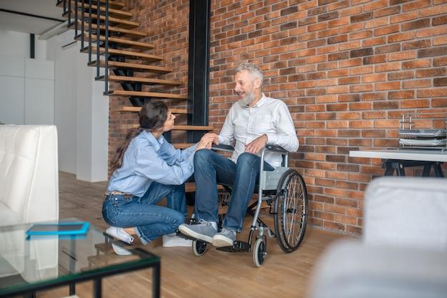 Um casal em casa. jovem de cabelos escuros sentada perto do marido deficiente