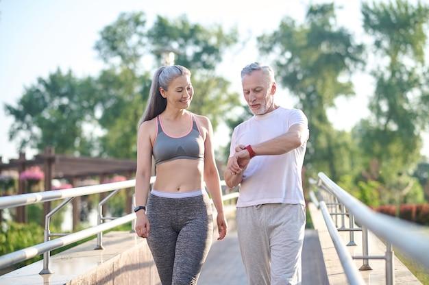 Um casal em roupas esportivas verificando o pulso depois de correr