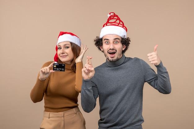 Um casal está parado ao lado da árvore de natal