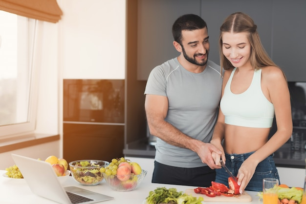 Um casal está preparando uma salada no café da manhã.