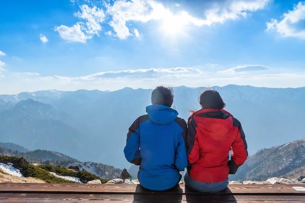 Um casal está vendo a paisagem do monte tsubakuro dake ao pôr do sol. cordilheira do parque chubu-sangaku dos alpes do norte de japão.