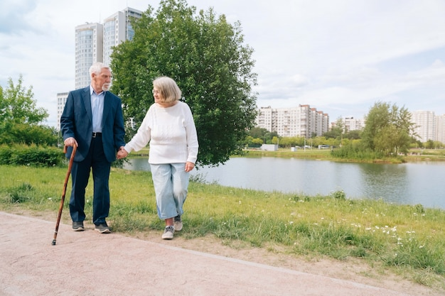 Um casal europeu adulto anda pela cidade. um passeio ao ar livre os avós andam pela mão na cidade.