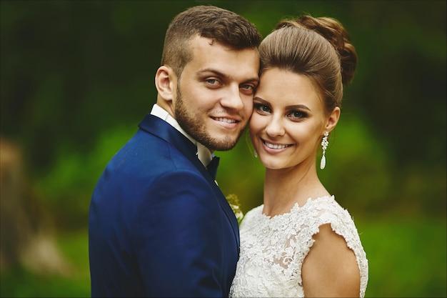 Um casal feliz de noivos se abraçando e olhando para a câmera.