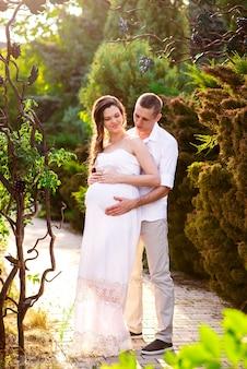 Um casal feliz e grávida está caminhando na natureza.