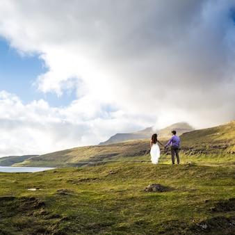 Um casal feliz em vestidos de noiva ou a noiva e o noivo de mãos dadas e olhando a natureza. ilhas faroe