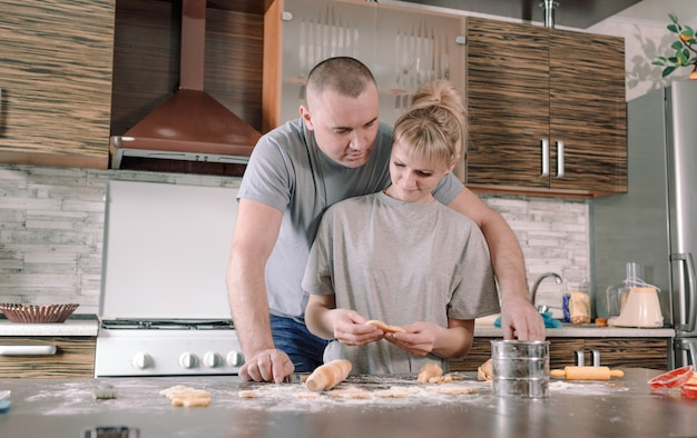 Um casal feliz prepara biscoitos na cozinha. preparação de comida conjunta