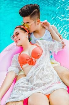 Um casal feliz, relaxando em uma piscina
