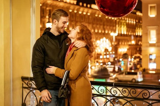 Um casal feliz se abraça na rua à noite sob as luzes festivas