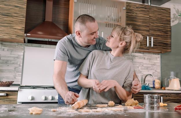Um casal feliz se olha e sorri enquanto faz biscoitos na cozinha. o conceito de felicidade na família