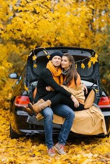 Um casal feliz se senta no porta-malas de um carro, apreciando a vista do outono. o conceito de viagens e feriados de fim de semana.