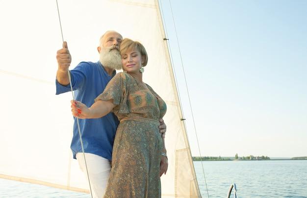 Um casal feliz sênior navegando e sentado ao volante de um barco a vela no lago.