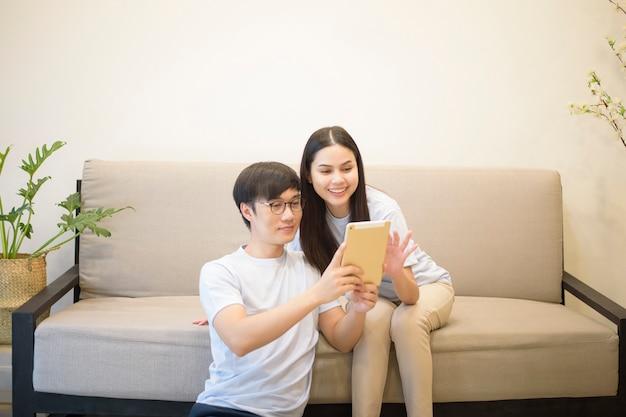 Um casal feliz, vestindo camisa azul é relaxante e segurando um tablet em um sofá em casa