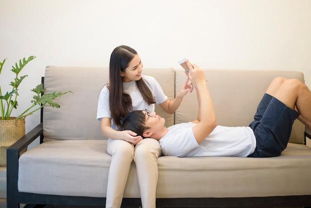 Um casal feliz, vestindo camisa azul está mentindo e segurando um tablet em um sofá em casa