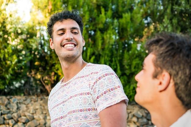 Um casal gay passeando dois caras sorridentes conversando um encontro romântico de férias casal gay
