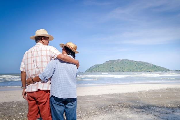 Um casal idoso asiático se abraçando na praia