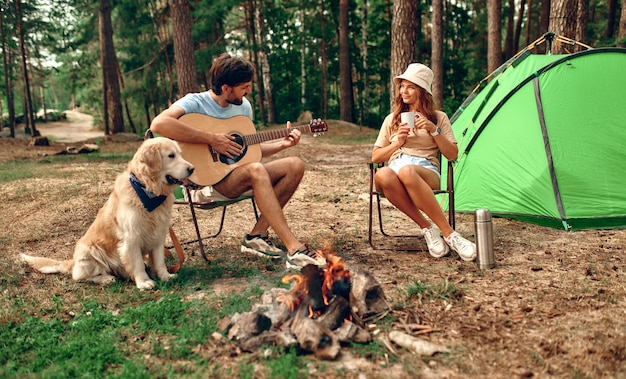 Um casal jovem e amoroso senta-se perto de uma fogueira e de uma barraca, bebe café e toca violão com um cão labrador em uma floresta de pinheiros. acampar, recreação, caminhadas.