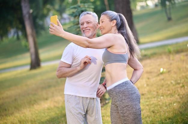 Um casal maduro e feliz fazendo selfie e parecendo satisfeito