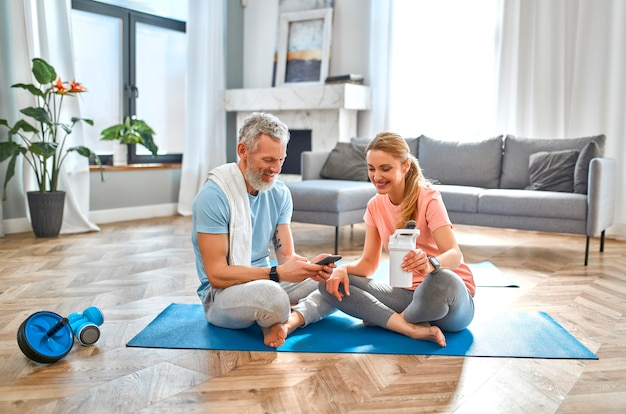 Um casal maduro está descansando após um treino, bebendo um shake de proteína e usando o telefone em casa.