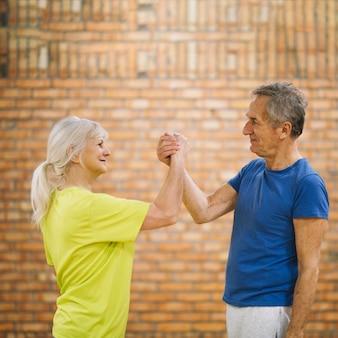 Um casal mais velho apertando as mãos na academia