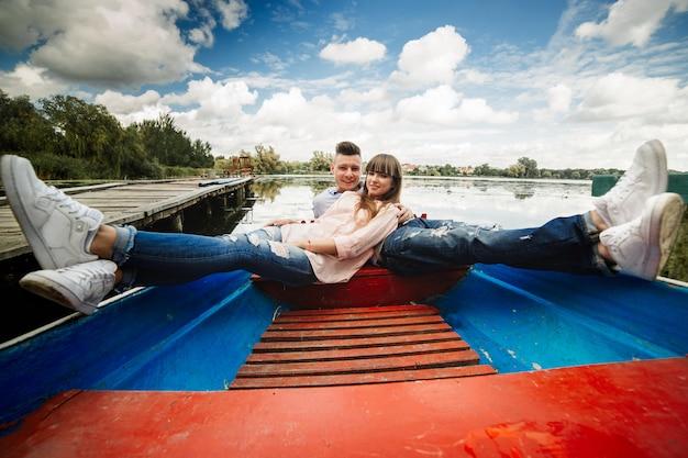 Um casal montando um barco azul em um lago. romance. casal emocional. engraçado e apaixonado