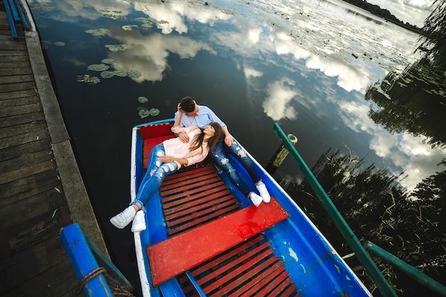 Um casal montando um barco azul em um lago. romance. casal emocional.