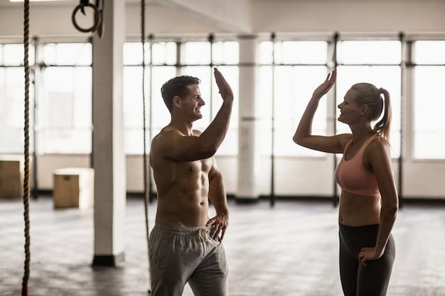 Um casal muscular aplaudindo as mãos