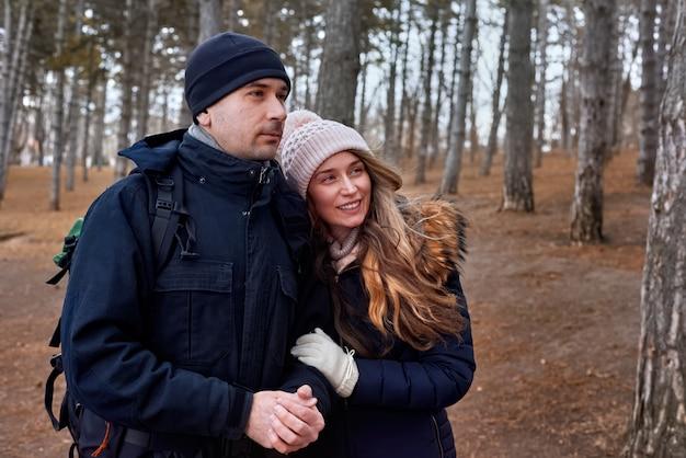 Um casal na floresta de fim de inverno com mochila