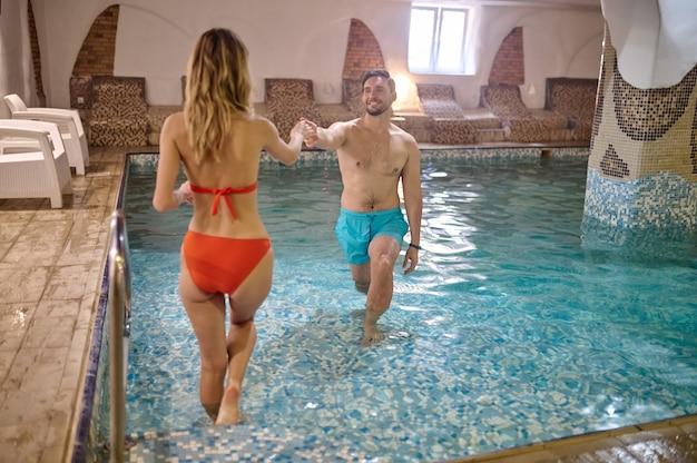 Um casal na piscina de mãos dadas e olhando um para o outro