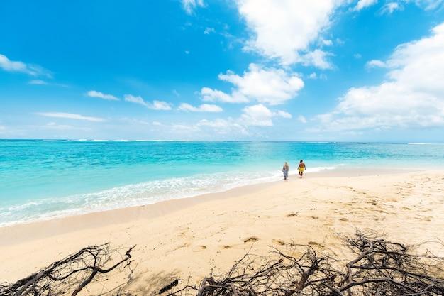 Um casal na praia de le morne brabant, maurícia, no oceano índico.