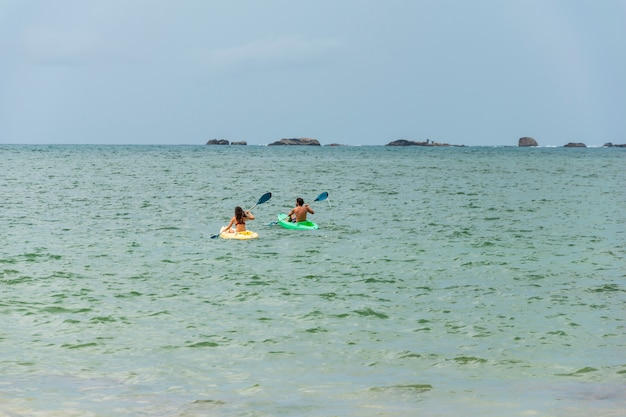 Um casal nada em um caiaque ou canoa no mar ou oceano. conceito de caiaque ou canoagem com as pessoas. espaço para texto