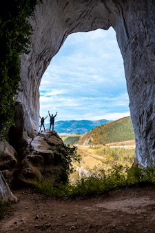 Um casal nas cavernas de ojo de aitzulo em oñati com os braços levantados