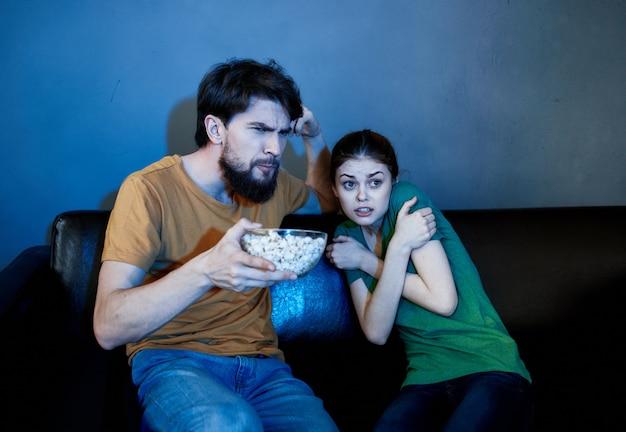 Um casal no sofá assistindo tv e pipoca dentro de casa