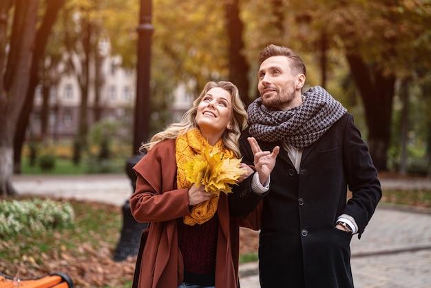 Um casal num encontro olhando para cima andando no parque outono de mãos dadas. foto ao ar livre de um jovem