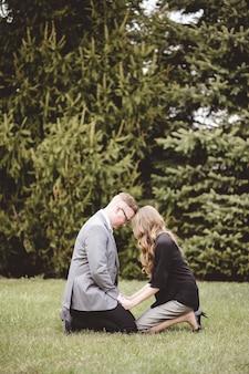 Um casal orando juntos de joelhos em um gramado com árvores ao fundo