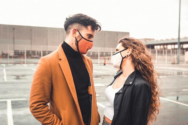 Um casal posando na rua com roupas casuais