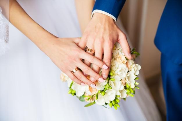 Um casal recém-casado coloca as mãos em um buquê de casamento mostrando seus anéis de casamento.