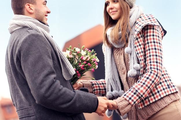 Um casal romântico com flores se encontrando na cidade