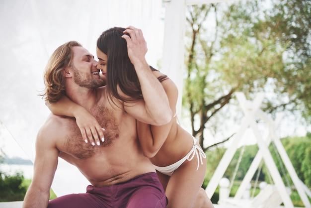 Um casal romântico na praia em um maiô, gente jovem bonita e sexy.
