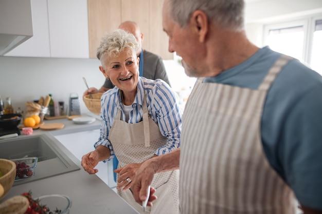 Um casal sênior com amigos fazendo festa dentro de casa, conversando enquanto cozinha.