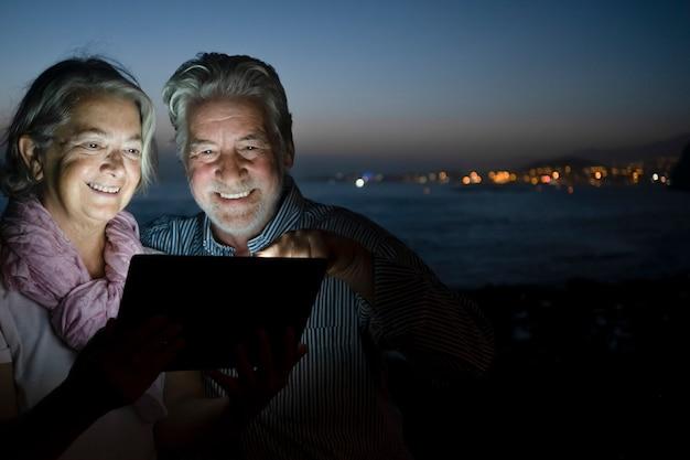 Um casal sênior sentado na praia com um laptop iluminando seus rostos. noite escura e costa marítima iluminada