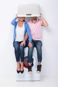 Um casal senta em uma máquina de lavar roupa e cobre seus rostos.