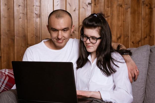 Um casal sentado em casa no sofá com um laptop encomendar mercadorias on-line