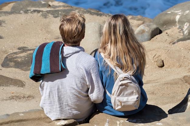 Um casal sentado nas rochas e olhando para o oceano de san diego, eua