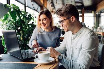 Um casal sentado no café rindo alegremente, olhando para a tela do laptop
