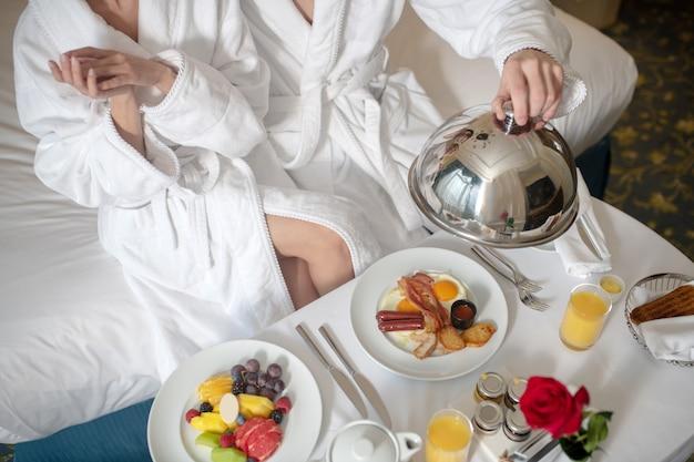 Um casal tomando um café da manhã nutritivo no quarto do hotel