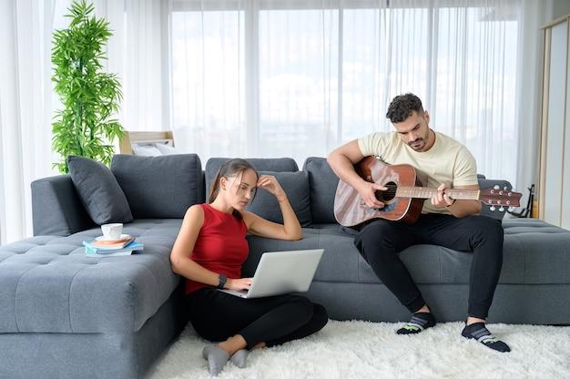Um casal trabalhando em casa junto com alegria e boa emoção