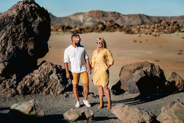 Um casal, uma mulher e um homem na cratera do deserto do vulcão teide e apreciam a vista do pôr do sol. viagem às montanhas, liberdade e o conceito de um estilo de vida ativo. ilhas canárias, espanha.